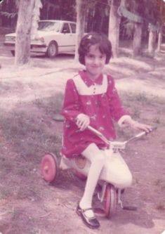 Raya, en Irak, montando un triciclo en su infancia