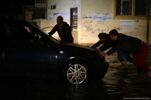 Los habitantes de Gaza intentan mover un automóvil después de que las lluvias torrenciales bloquearan las carreteras, 27 de noviembre de 2017 [Mohammed Asad / Middle East Monitor]