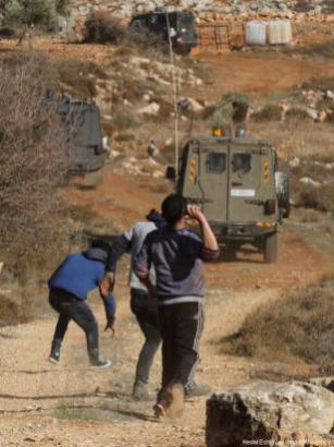 Palestinos arrojan piedras a los soldados israelíes después de que un agricultor palestino fuese asesinado a tiros por colonos judíos en la aldea de Khusra de Nablus, en Cisjordania, 30 de noviembre de 2017.Tras este enfrentamiento, el grupo de palestinos detuvo a los colonos judíos en una cueva y los soldados israelíes llegaron al lugar y recibieron a estos colonos judíos detenidos. [Agencia Nedal Eshtayah / Anadolu]