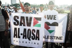 """Los manifestantes muestran una pancarta que dice """"Apoyo a Al-Aqsa y Palestina"""" en la manifestación para apoyar a Palestina en el Monumento Nacional en Yakarta, Indonesia,17 de diciembre de 2017 [Agencia Nani Afrida / Anadolu]"""