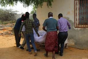 Un grupo de personas recoge los cuerpos de las víctimas tras los ataques perpetrados cerca del edificio de la Agencia Nacional de Inteligencia y Seguridad de Somalia (NISA) en Mogadiscio, Somalia, 24 de febrero de 2018 [Agencia Sadak Mohamed / Anadolu]