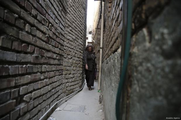 Diferentes personas pasan por el callejón más estrecho de Bagdad, Iraq, que tiene 30 centímetros de ancho y 70 metros de largo, llamado 'derbune' por la población local, 15 de enero de 2018 [Murtadha Sudani / Agencia Anadolu]