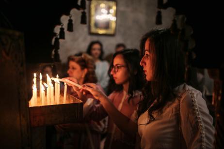 Cristianas ortodoxas encienden velas durante la procesión del Domingo de Ramos en la ciudad de Gaza, 1 de abril de 2018. En el Domingo de Ramos se celebra la entrada de Jesucristo en Jerusalén y se colocan en su camino las ramas de palma. (Mustafa Hassona - Agencia Anadolu)
