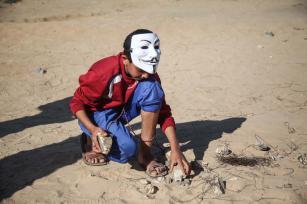 """Un joven recoge piedras para tirarlas contra las fuerzas de seguridad israelíes que usan gas lacrimógeno y munición real contra los palestinos concentrados con motivo de la """"Marcha del Retorno"""", en la que exigen su derecho al retorno y la eliminación del bloqueo israelí, Gaza, 1 de abril, 2018 (Hassan Jedi - Agencia Anadolu)"""