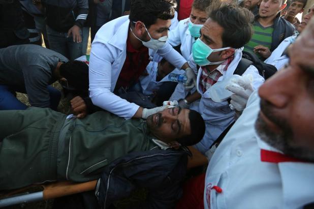Palestinos llevan a un herido a causa de los ataques de las fuerzas de seguridad israelíes, Gaza, 1 de abril, 2018 (Hassan Jedi - Agencia Anadolu)
