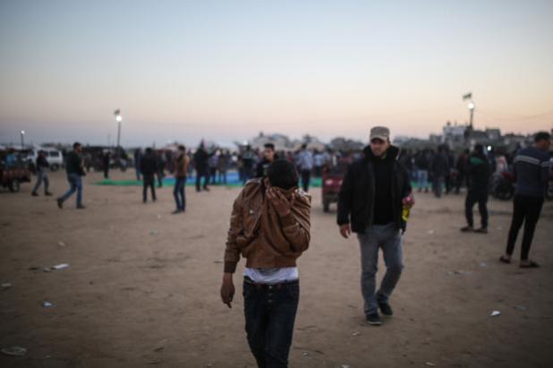 """Palestinos cubren sus caras para protegerse del gas lacrimógeno usado por las fuerzas israelíes contras los palestinos manifestados por el """"Día de la Tierra"""", que conmemora el asesinato de seis palestinos por las fuerzas israelíes en 1976, en Khan Yunis, Gaza, 1 de abril de 2018 (Ashraf Amra- Anadolu Agency)"""