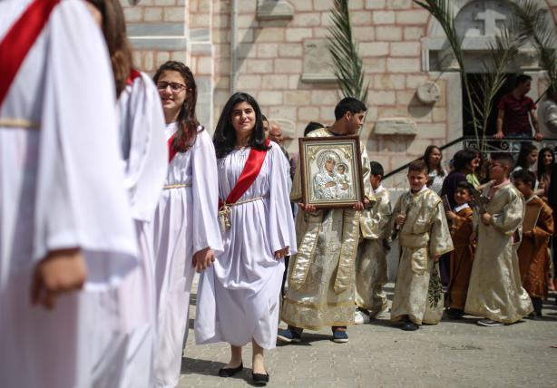 Cristianos ortodoxos asisten a la procesión del Domingo de Ramos en la ciudad de Gaza, 1 de abril de 2018. En el Domingo de Ramos se celebra la entrada de Jesucristo en Jerusalén y se colocan en su camino las ramas de palma. (Mustafa Hassona - Agencia Anadolu)
