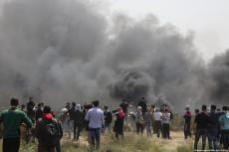 """Manifestantes palestinos se cubren después de que las fuerzas israelíes dispararan durante las manifestaciones por la """"Gran Marcha del Retorno"""", 6 de abril de 2018 [Mohammed Asad / Middle East Monitor]"""