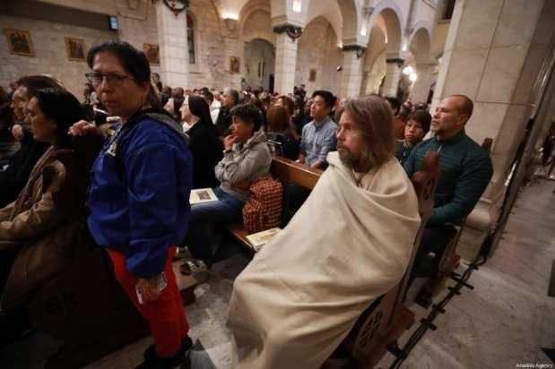Los cristianos palestinos asisten a la misa navideña en la Iglesia de Santa Catalina para dirigir el ritual con motivo de la Navidad en Belén, Cisjordania, el 24 de diciembre de 2019 [Issam Rimawi / Agencia Anadolu]