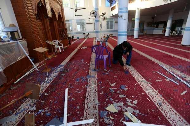 Un palestino limpia fragmentos de cristal en la mezquita de Al-Vedud después de los ataques de aviones de combate israelíes
