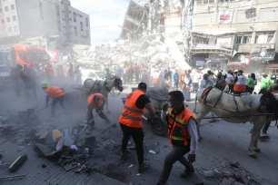 Voluntarios palestinos barren los escombros de los edificios destruidos por los ataques israelíes en la ciudad de Gaza [Mohammed Asad/Middle East Monitor].