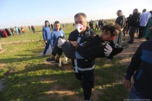 Paramédico carrega uma criança ferida após tiros disparados por soldados israelenses contra palestinos durante a Grande Marca do Retorno, em 8 de fevereiro de 2019 [Mohammed Asad/Middle East Monitor]