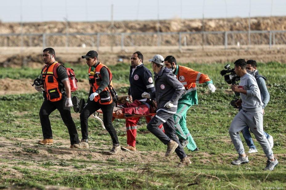 Paramédicos palestinos carregam um homem ferido após forças de segurança israelenses investirem contra manifestantes palestinos em protestos da Grande Marcha do Retorno, no bairro de Shuja'iyya, Cidade de Gaza, 1° de fevereiro de 2019 [Ali Jadallah/Agência Anadolu]