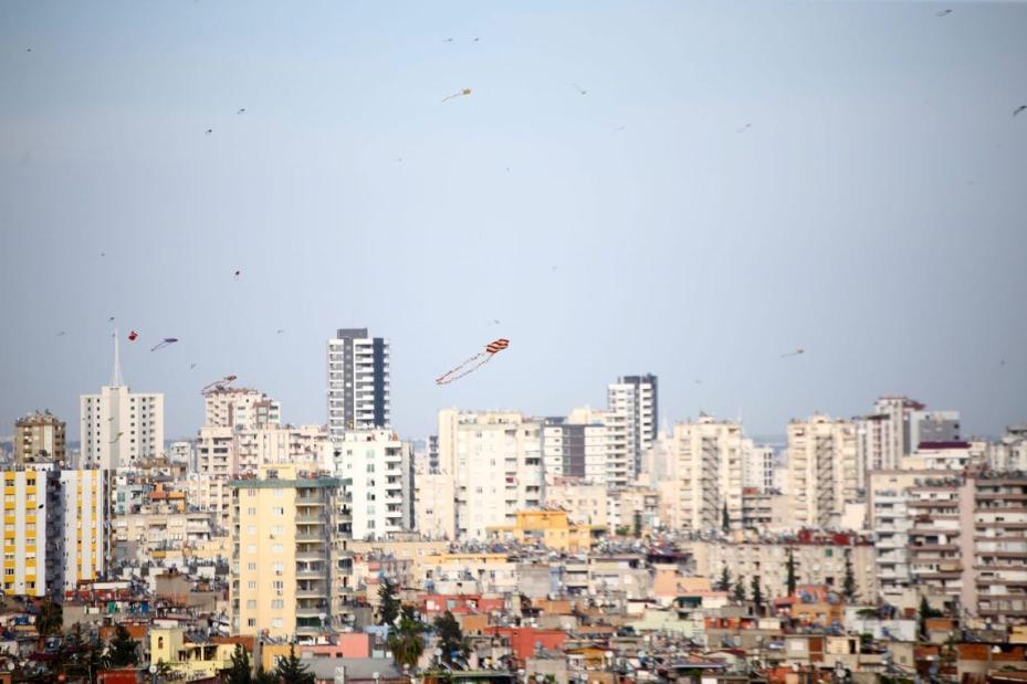 Pessoas empinam pipas do telhado de sua casas durante a quarentena, após restrições serem restabelecidas em 31 províncias turcas por dois dias, como parte das medidas de prevenção contra o coronavírus (covid-19), em Adana, Turquia l, 18 de abril de 2020. [Eren Bozkurt/Agência Anadolu]