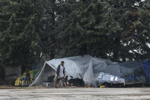 Homem caminha no campo de refugiados de Malakasa após um homem ser testado positivo para coronavírus o acampamento ser colocado em quarentena, em Atenas, Grécia, em 5 de abril de 2020 [Ayhan Mehmet - Agência Anadolu]