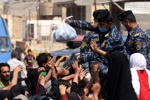 Forças de segurança iraquianas distribuem alimento para pessoas em necessidade durante a pandemia de coronavírus (covid-19), em Bagdá, capital do Iraque, 13 de abril de 2020 [Murtadha Al-Sudani/Agência Anadolu]