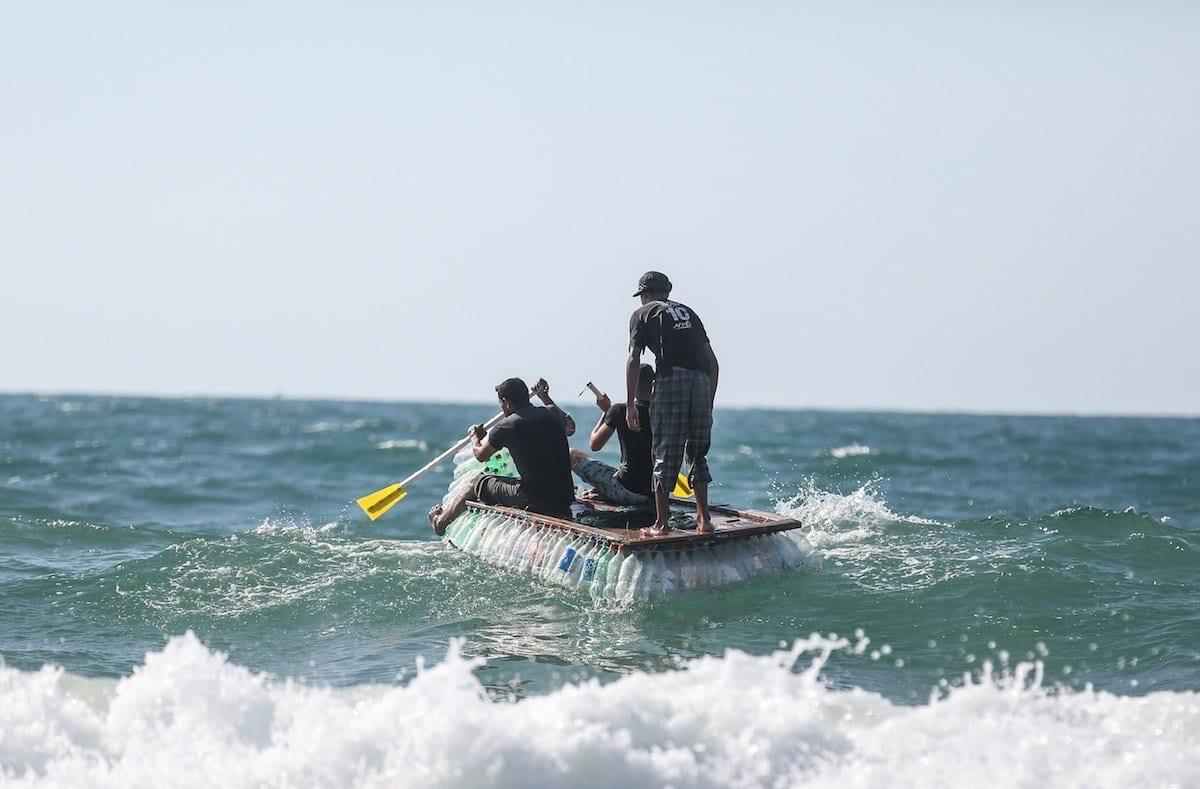 Pescador palestino Abu Zaid navega em seu barco manufaturado com cerca de 700 garrafas plásticas, na costa da Cidade de Gaza [Mustafa Hassona/Agência Anadolu]