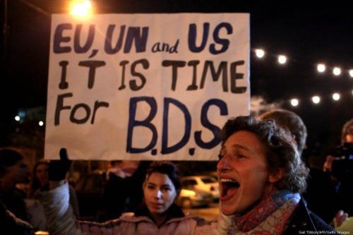 Manifestantes seguram um cartaz pedindo à comunidade internacional que apóie a campanha de Boicote, Desinvestimento e Sanções (BDS) [Gali Tibbon / AFP / Getty Images]