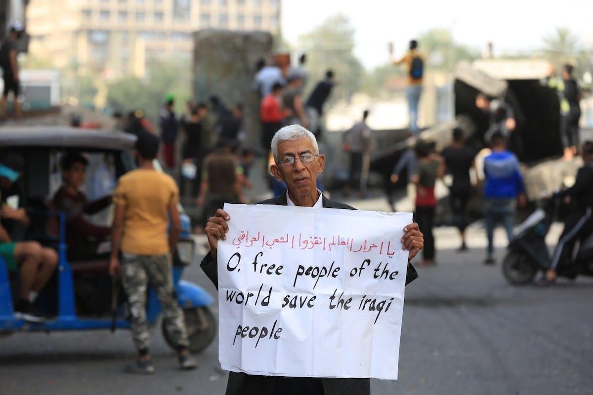 """Cidadão idoso segura um cartaz durante protesto contra o governo na Praça Al-Khulani, em Bagdá, Iraque, 6 de março de 2020. No cartaz, um apelo: """"Povo livre do mundo, salve o povo iraquiano"""" [Murtadha Al-Sudani/Agência Anadolu]"""