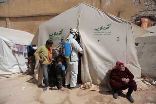 Diante do coronavírus, membros da Defesa Civil Síria (Capacetes Brancos) desinfectam construções provisórias e tendas onde famílias vivem aglomeradas, em Idlib, Síria, 24 de março de 2020 [Muhammed Said/Agência Anadolu]