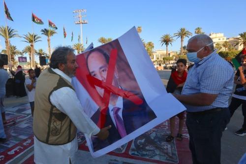Manifestantes exibem cartaz com o rosto marcado do Presidente do Egito Abdel Fattah el-Sisi, durante protesto contra ameaça de intervenção na Líbia, na Praça dos Mártires, em Trípoli, capital do país, 21 de junho de 2020 [Hazem Turkia/Agência Anadolu]