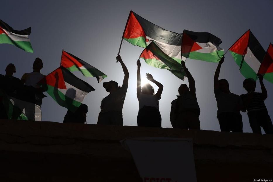 Manifestantes seguram bandeiras palestinas na Cisjordânia em 28 de setembro de 2019 [Issam Rimawi / Agência Anadolu]
