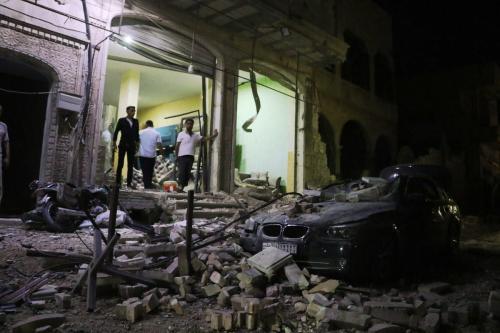 Mulher vasculha detritos após aviões de guerra russos realizarem ataques aéreos sobre o centro da cidade de Al-Bab, na Síria, em 15 de julho de 2020. [Mustafa Bathis - Agência Anadolu]