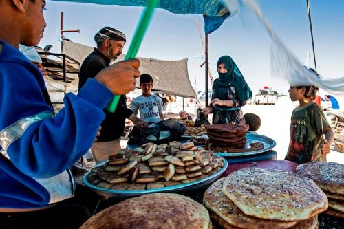 Sírios deslocados buscam comida em um campo de refugiados na Síria, em 10 de maio de 2020 [Delil Souleiman/ AFP/ Getty Images]