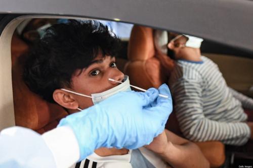Criança é testada para coronavírus dentro de um veículo em sistema driv, -thru no distrito de al-Khawaneej, Dubai, em 9 de abril de 2020. [Karim Sahib/ AFP via Getty Images]