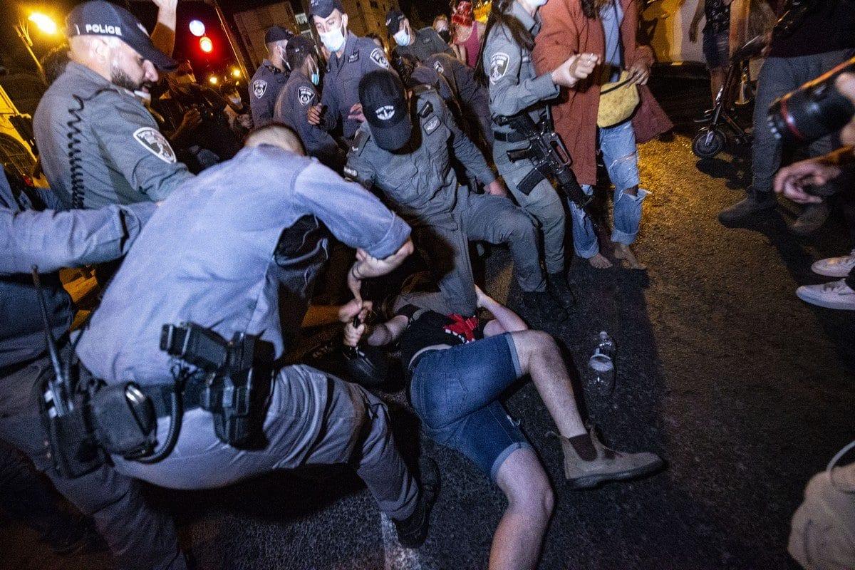 Forças de segurança prendem um manifestante durante uma manifestação contra o primeiro-ministro israelense Benjamin Netanyahu em Jerusalém em 21 de julho de 2020 [Mostafa Alkharouf/ Agência Anadolu]