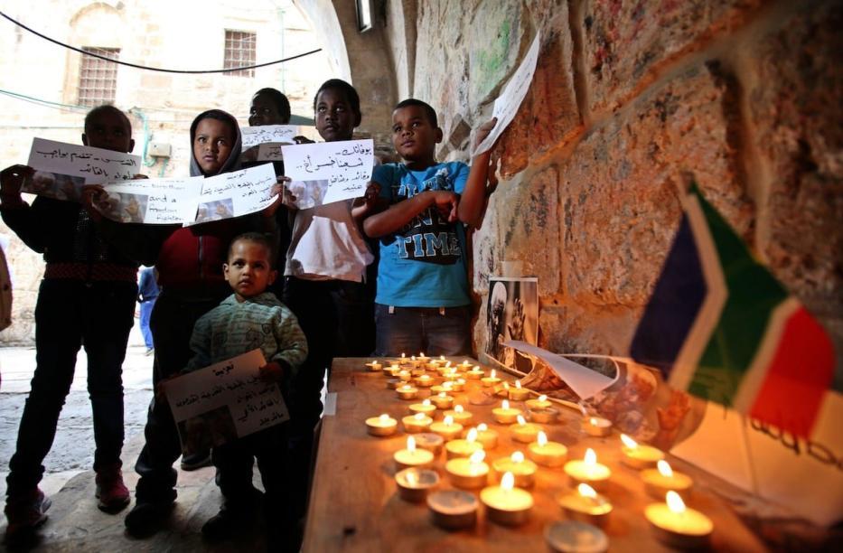 Palestinos reúnem ao redor de um memorial para o falecido presidente sul-africano Nelson Mandela, em área da Cidade Velha de Jerusalém habitada por muitos africanos, em 7 de dezembro de 2013 [Saeed Qaq/Apaimages]