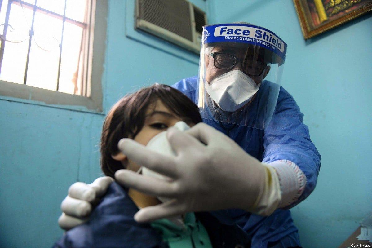 Médico egípcio ajusta máscara de proteção no rosto de um menino, na unidade de doenças infecciosas do hospital Imbaba, durante a crise da pandemia de coronavírus, no Cairo, capital do Egito, 19 de abril de 2020 [Ahmed Hasan/AFP/Getty Images]