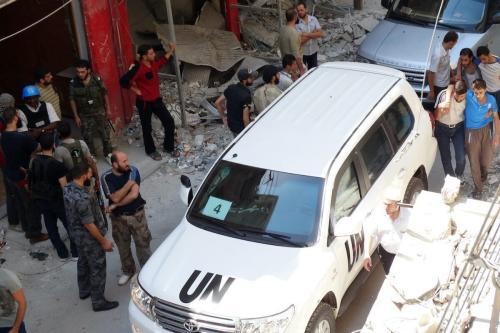 Sírios reúnem-se perto de um veículo de especialistas da ONU, que inspecionam o local suspeito de ser atingido por ataque químico mortal, na área de Ghouta Oriental, subúrbios de Damasco, 28 de agosto de 2013 [Mohamed Abdullah/AFP/Getty Images]