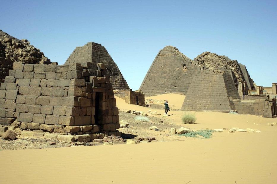 Visitante caminha entre as pirâmides, no sítio funerário de Meroe, norte de Cartum, Sudão [Ebrahim Hamid/AFP/Getty Images]