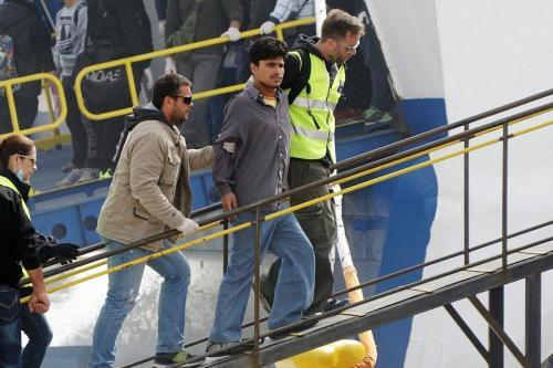 Oficial de fronteira escolta imigrante a bordo de um barco para retorná-lo à Turquia, no porto de Mitilene, na ilha grega de Lesbos, 8 de abril de 2016 [Stringer/AFP/Getty Images]