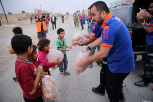 Crianças sírias recebem pacotes de auxílio alimentar na Síria, 19 de dezembro de 2019 [Behçet Alkan/Agência Anadolu]