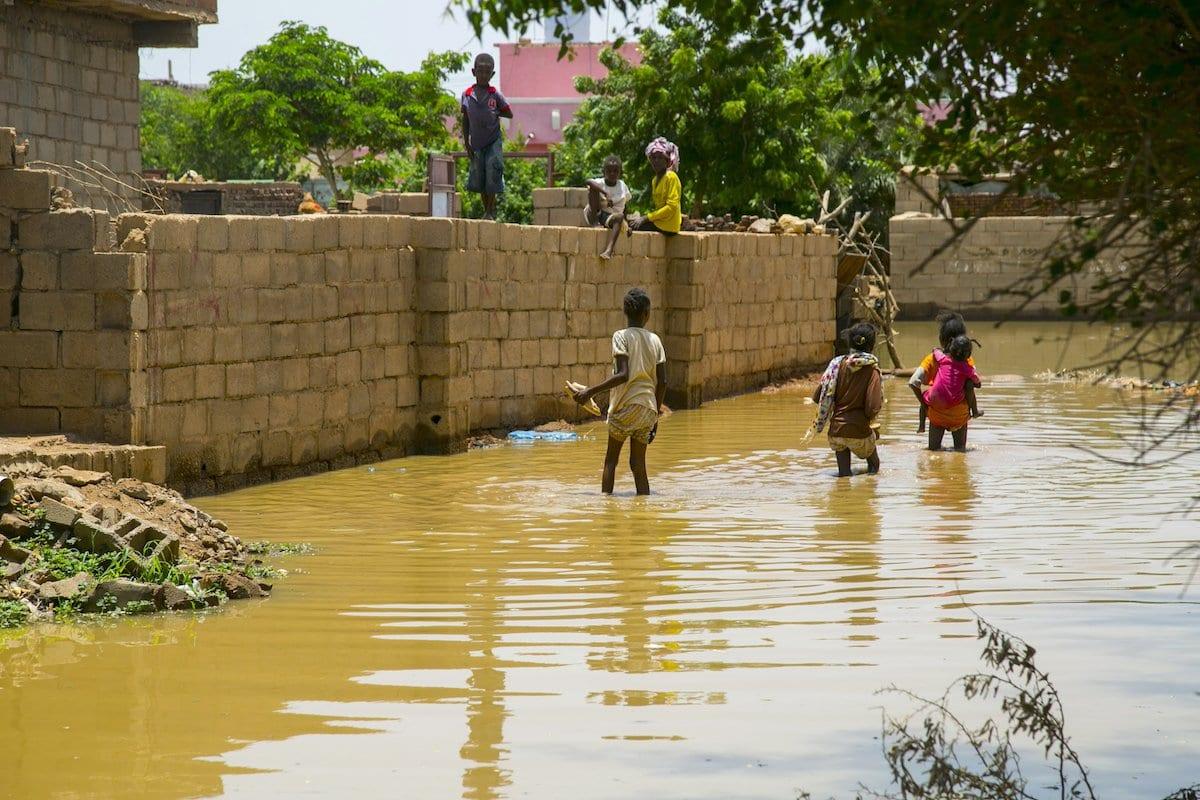 Crianças sudanesas tentam atravessar uma rua inundada no distrito de al-Qalqili, em Cartum, Sudão, 29 de agosto de 2020 [Mahmoud Hjaj/Agência Anadolu]