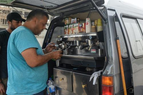 Refugiado sírio prepara café na traseira de um food truck improvisado no Cairo, em 23 de outubro de 2018. [Mohamed El-Shahed/ AFP via Getty Images]