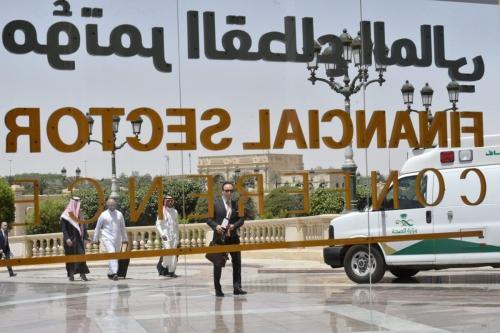Os participantes sauditas da Conferência do Setor Financeiro realizada em Riade, passam em frente a uma parede de vidro com inscrições do evento, em 24 de abril de 2019 . [Fayez Nureldine/ AFP via Getty Images]