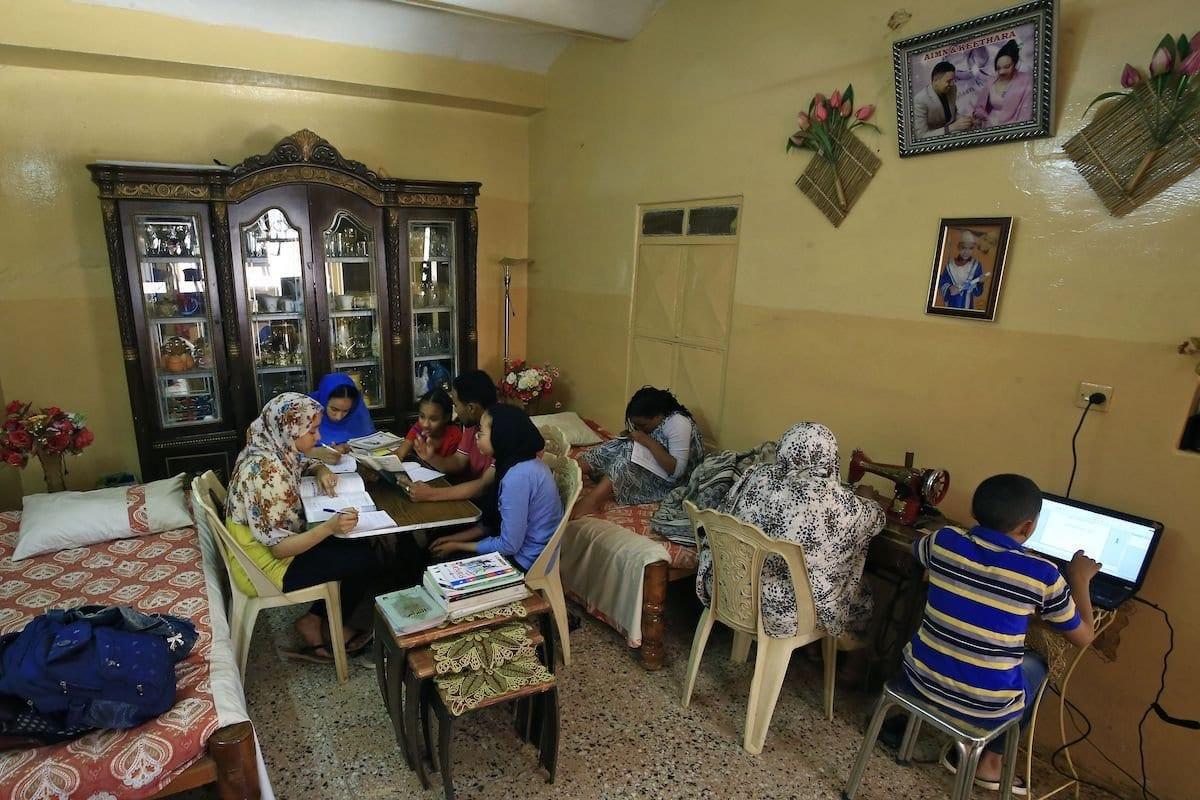 Esta imagem mostra membros de uma família estudando juntos em casa, em Khartoum, devido ao fechamento das escolas e universidades como medida preventiva contra a disseminação COVID-19, 23 de março de 2020 [ASHRAF SHAZLY / AFP via Getty Images].
