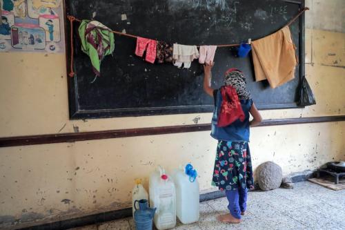 Menina estende um varal em uma sala de aula utilizada como abrigo por iemenitas deslocados pela guerra, na cidade de Taez, Iêmen, 23 de julho de 2020 [Ahmad Al-Basha/AFP/Getty Images]