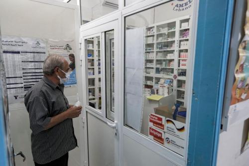 Homem com máscara devido à pandemia de coronavírus COVID-19, aguarda medicamento na farmácia da ong Amel na cidade costeira de Tiro no sul do Líbano em 22 de julho de 2020 [Joseph Eid/ AFP via Getty Images]