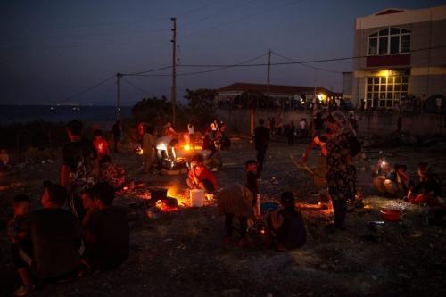 Refugiados e migrantes do acampamento destruído de Moria cozinham em chamas durante o início da noite na ilha de Lesbos, em 11 de setembro de 2020. - [Angelos Tzortzinis/ AFP via Getty Images]