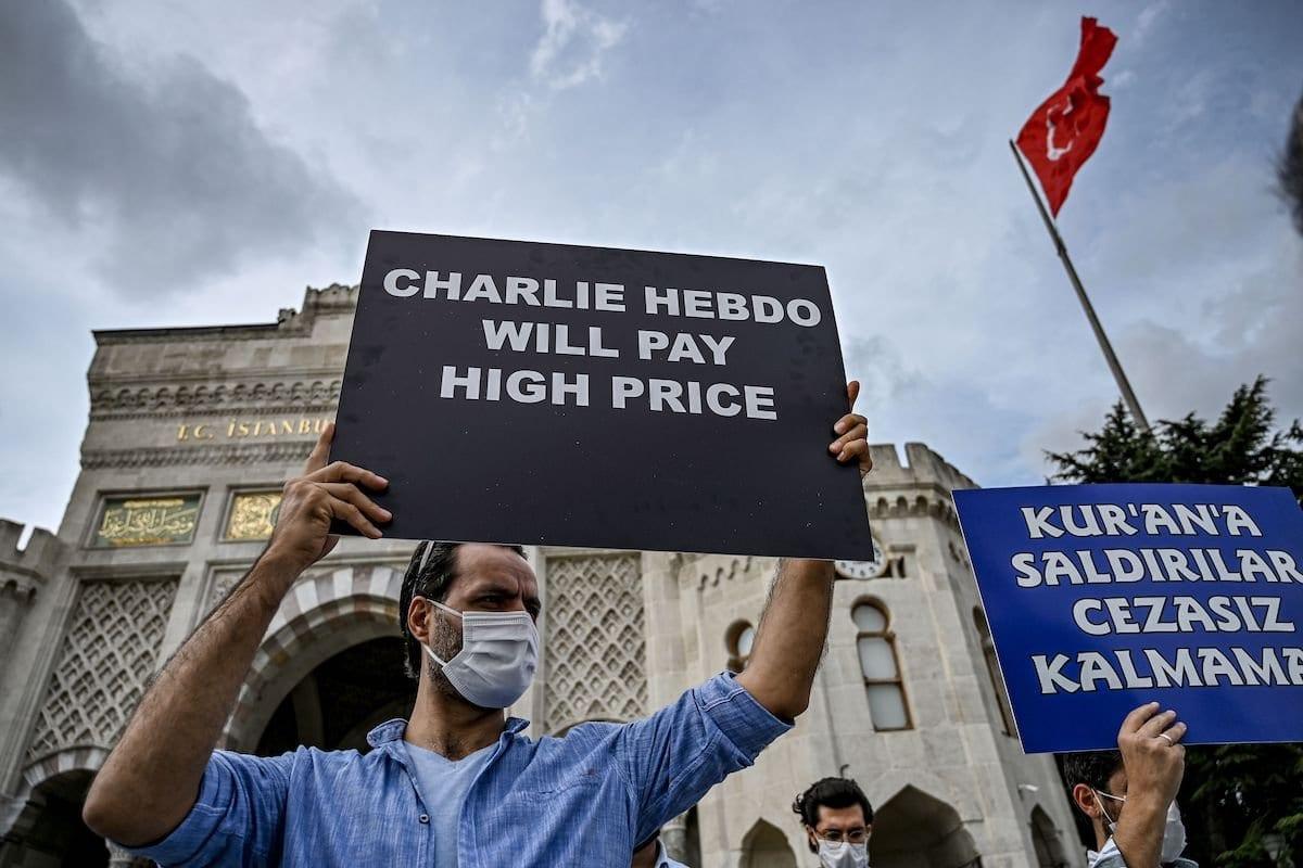 Manifestantes entoam slogans e seguram cartazes contra a França e o presidente francês em Istambul,13 de setembro de 2020 [OZAN KOSE / AFP via Getty Images]
