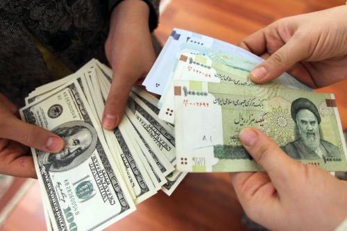 Iranianos contando e trocando notas de 100 dólares dos Estados Unidos e notas de Rial do Irã, em 12 de janeiro de 2012 [ Atta Kenare/ AFP via Getty Images]