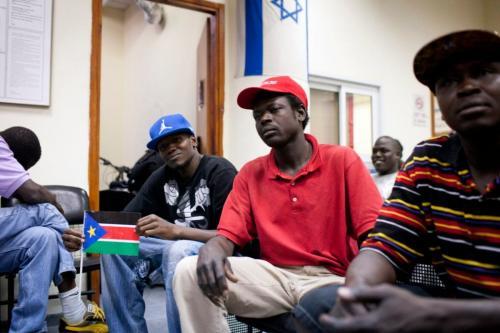 Refugiado do Sudão do Sul segura sua bandeira nacional enquanto é mantido ao lado de outros refugiados em um centro de detenção em Holon, ao sul de Tel Aviv, 11 de junho de 2012. [OREN ZIV / AFP / GettyImages]