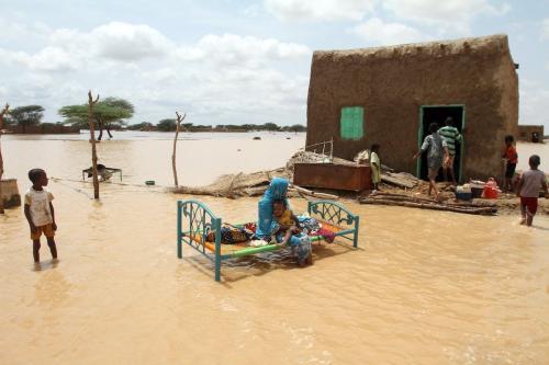 Uma mulher sudanesa está sentada com seu filho ao lado de sua casa em uma rua inundada nos arredores da capital Cartum [ASHRAF SHAZLY / AFP via Getty Images].