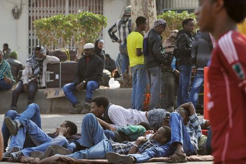 Trabalhadores estrangeiros esperam com seus pertences antes de embarcar nos ônibus da polícia que os transferem para um centro de deportação em Riade, Arábia Saudita, em 14 de novembro de 2013 [Fayez Nureldine/ AFP / Getty Images]