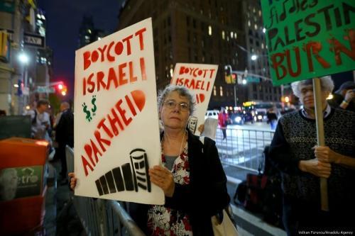 Ativistas de direitos humanos exibem cartazes contra o apartheid israelense e a ocupação na Palestina, em Nova Iorque, Estados Unidos, 25 de outubro de 2017 [Volkan Furuncu/Agência Anadolu]