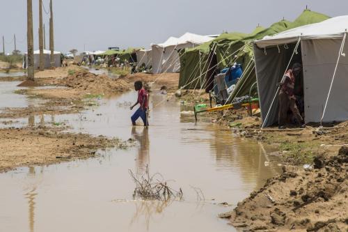 Pessoas carregam seus pertences em uma área submersa após enchentes causadas pela forte chuva no Sudão em 3 de agosto de 2020 [Mahmoud Hjaj / Agência Anadolu]